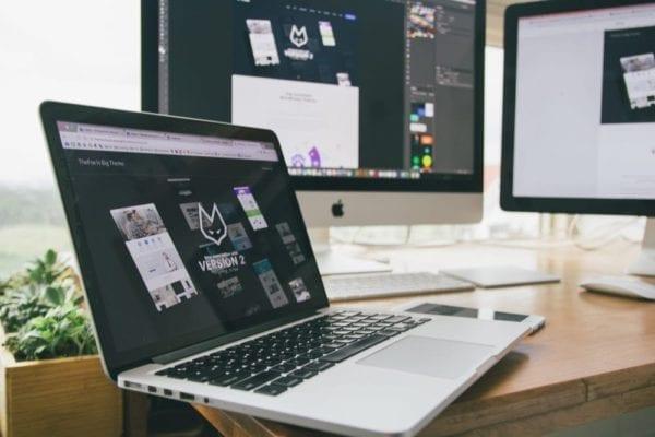 laptop on desk with desktops n background displaying website